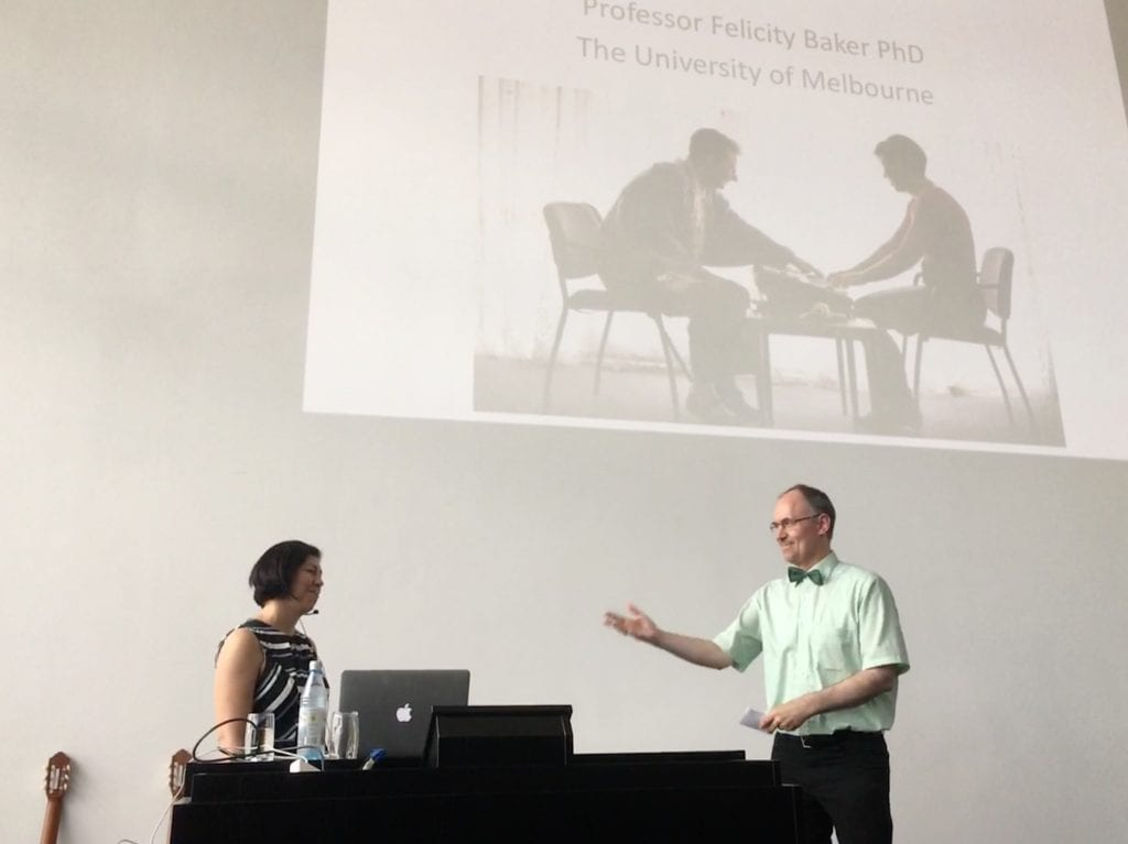 Professor Felicity Baker is introduced in Würzburg by her German Music Therapy colleague Professor Thomas Wosch. Image supplied.