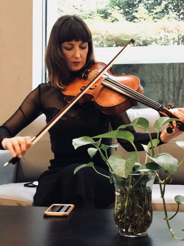 Violist Cecilla Dowling tunes up backstage in Shanghai. By Paul Dalgarno.