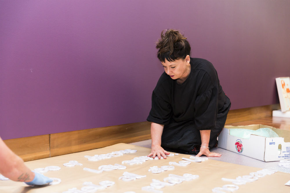 Dr Kate Daw prepares an installation work at the recent All the better to see you with: Fairy tales transformed exhibition at the Ian Potter Museum of Art. By Drew Echberg.