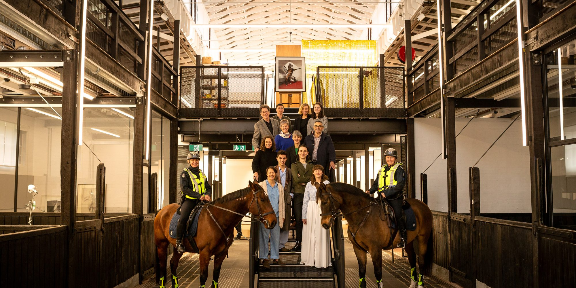 Victoria Police Mounted Branch members Monika Kusnierz (with Bob) and Christine Atherton (with Unity), flank Faculty of Fine Arts and Music students and staff, and architect Kerstin Thompson, in the refurbished Stables building. By Sav Schulman.