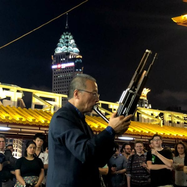 Tour translator and ethnomusicologist Wang Zheng-Ting gives a sheng (Chinese mouth organ) performance on board a cruise boat on the Huangpu River. By Paul Dalgarno.