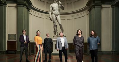 L-R Sam Kreusler, Danna Yun, Jack Riley, Associate Professor Matt Delbridge, Esther Stewart and Ash Perry at the feet of Michelangelo's statue of David, Galleria dell' Accademia, Florence. By O'Rourke & Gates.